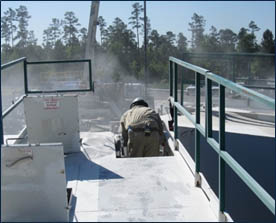 Silica dust cloud by worker delivering sand from sand mover to transfer belt - Photo credit-NIOSH