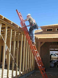 Construction worker on a portable ladder at proper angle against building under construction