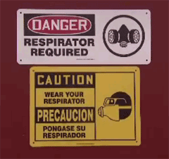 Danger sign regarding a respirator being required and a Caution sign in English/Spanish noting wear your respirator