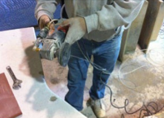 A worker uses an angle grinder with a polishing pad to finish a stone countertop. The water-fed tool helps reduce exposure to respirable crystalline silica dust generated during grinding and polishing operations.