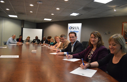 Eileen O'Laughlin, program manager, Georgia Department of Economic Development; Christi Griffin, OSHA's Atlanta-West area director; and Scott Shelar, executive director, Construction Education Foundation of Georgia; and other alliance members signing the renewal agreement.