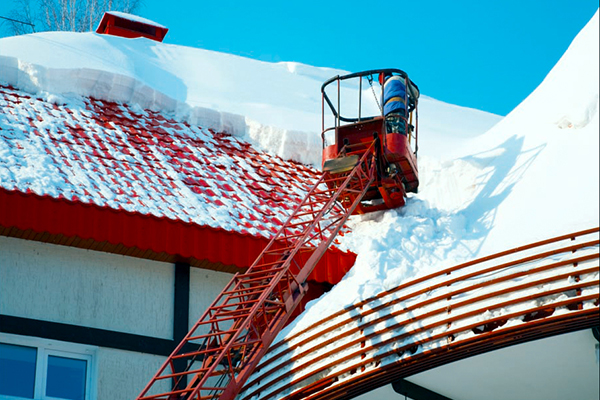 Image of worker on a lift clearing heavy snow from a roof