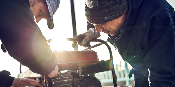 Photograph of a workers with a portable generator | Copyright iStock: skynesher - 507692990