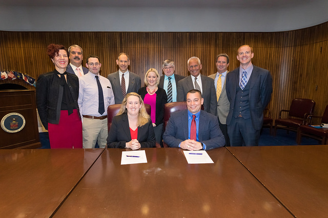 "Deputy Assistant Secretary Loren Sweatt, USDOL-OSHA and William ""Butch"" Chapman, President IWCA (seated, center), with representatives of IWCA and OSHA at the Alliance signing ceremony on February 14, 2018."