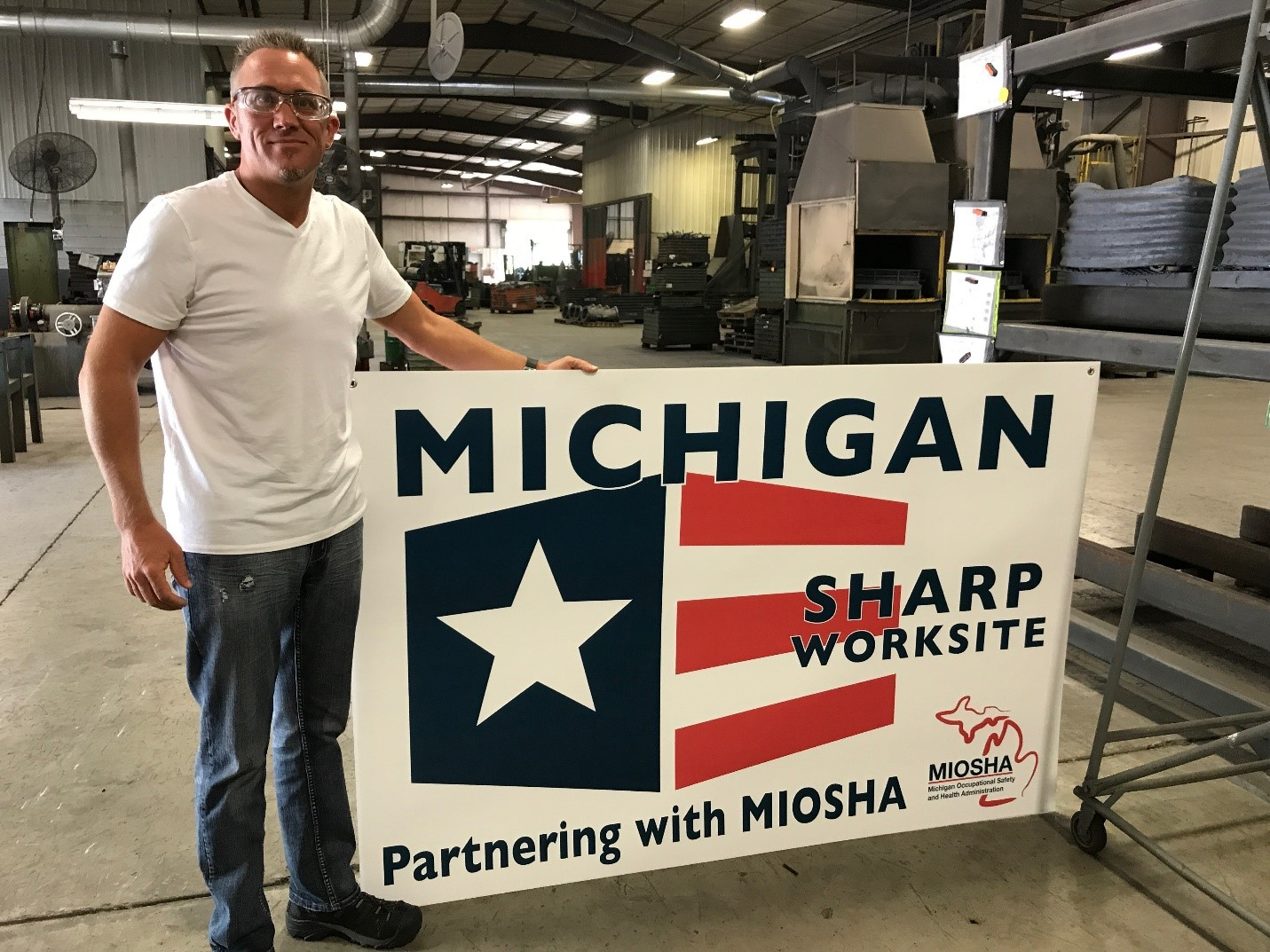 Mark Swanson, Quality/Safety Manager, with SHARP Banner