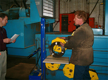 Figure 2: Employee replacing baler wire spool