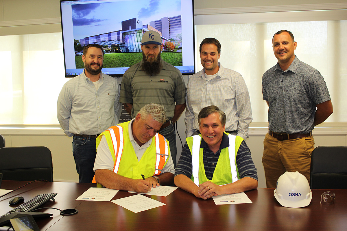 back row left to right): Kris Montgomery, Project Manager, McCarthy Construction Companies; Andy Parrish, Assistant Project Safety Manager, McCarthy Construction Companies; Ryan Sawall, Project Director, McCarthy Construction Companies; Steve Miller, Divisional Safety Director, McCarthy Construction Companies. (front row left to right): Darwin Craig, Assistant Area Director, Omaha Area Office, US DOL-OSHA, signing the agreement and Jeff Funke, Area Director, Omaha Area Office, US DOL-OSHA.