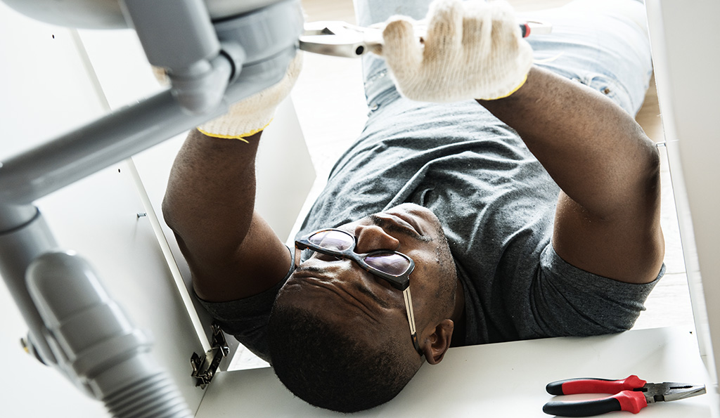 Plumber man fixing kitchen sink | Photo Credit: iStockphoto-929473012 | Copyright: Rawpixel
