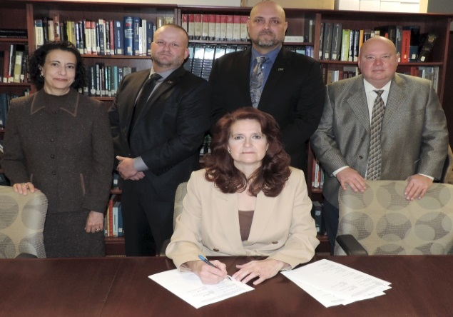OSHA Regional Administrator Kimberly Stille (seated) joins (from left) OSHA Acting Deputy Regional Administrator Dee Cantu, Business Manager for Local Union No. 10 Dave Coleman, President and Director of Training for the MO-KAN Ironworkers Apprenticeship Training Fund Brian Garrett, and Executive Director of Safety and Health for the Ironworkers International Steve Rank, for the signing of the partnership agreement.