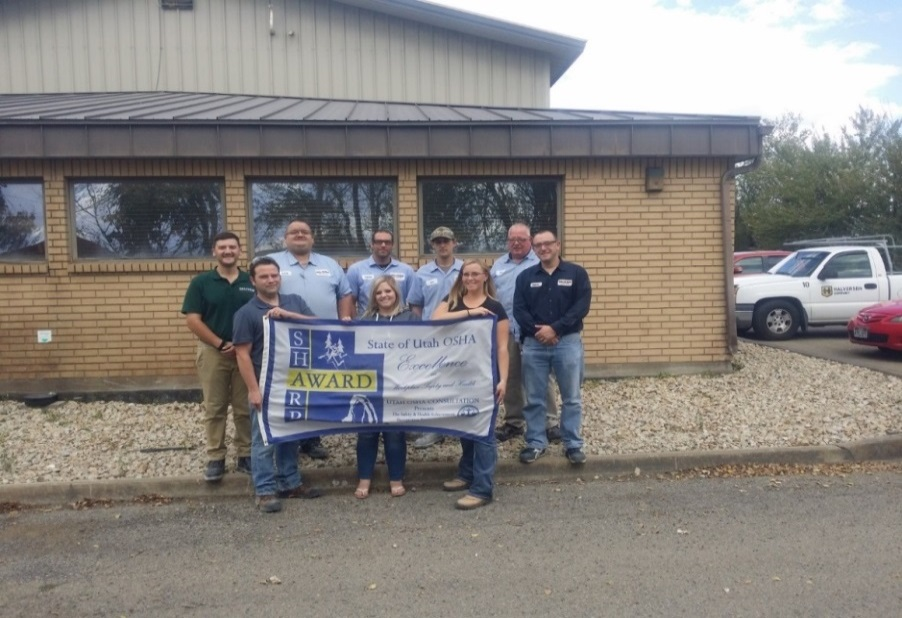 Back Row (Left to Right): Brandon Evans, Kenneth Burt, Andrew Christiansen, Alix Long, Richard Humphries, Andrew Higgins; Front Row (Left to Right, holding the banner): Quinn Morrill, Ashley Perry, Rebecca Taylor