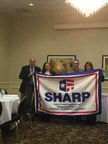 Sam Gualardo presents the SHARP flag to Karina Kolm, Safety Coordinator; Tom Hutchison, Plant Manager; and Patty Sweasy, Safety Manager