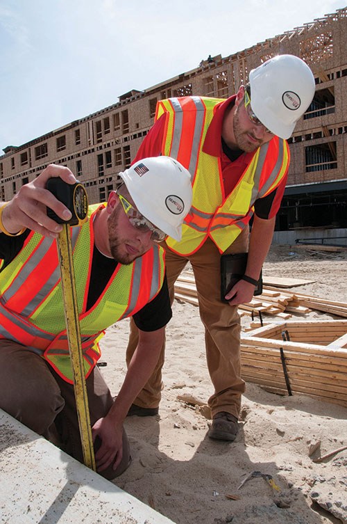 Photo by Karen Bachelder  Matt Hardy, construction safety consultant at WorkWISE NH (left), and intern Brady Keene, a senior at Keene State, measure a concrete ledge at A.W. Rose Construction's Bedford worksite.