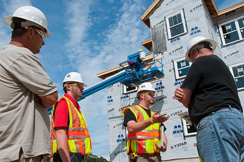 Photo by Karen Bachelder  Matt Hardy (center) chats with Gus Gustafson, construction manager/site supervisor at A.W. Rose Construction (right), as intern Brady Keene looks on. Gustafson has utilized the free on-site consultation service since getting fined by OSHA for improper window protection.