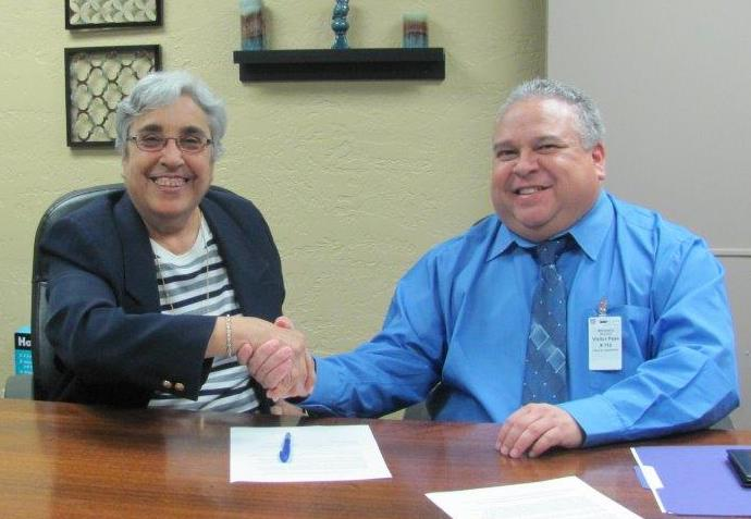 Caption: Margaret Arreola, David L. Carrasco Job Corps Center director (left) and Diego Alvarado Jr., OSHA area director in El Paso (right) sign the alliance agreement at the Job Corps center in El Paso.