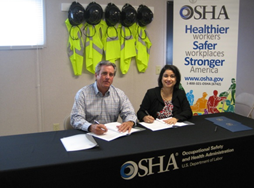 Lee Lewis, chief executive officer with Lee Lewis Construction Co., signs OSHA alliance agreement with Elizabeth L. Routh, OSHA's area director in Lubbock, Texas.