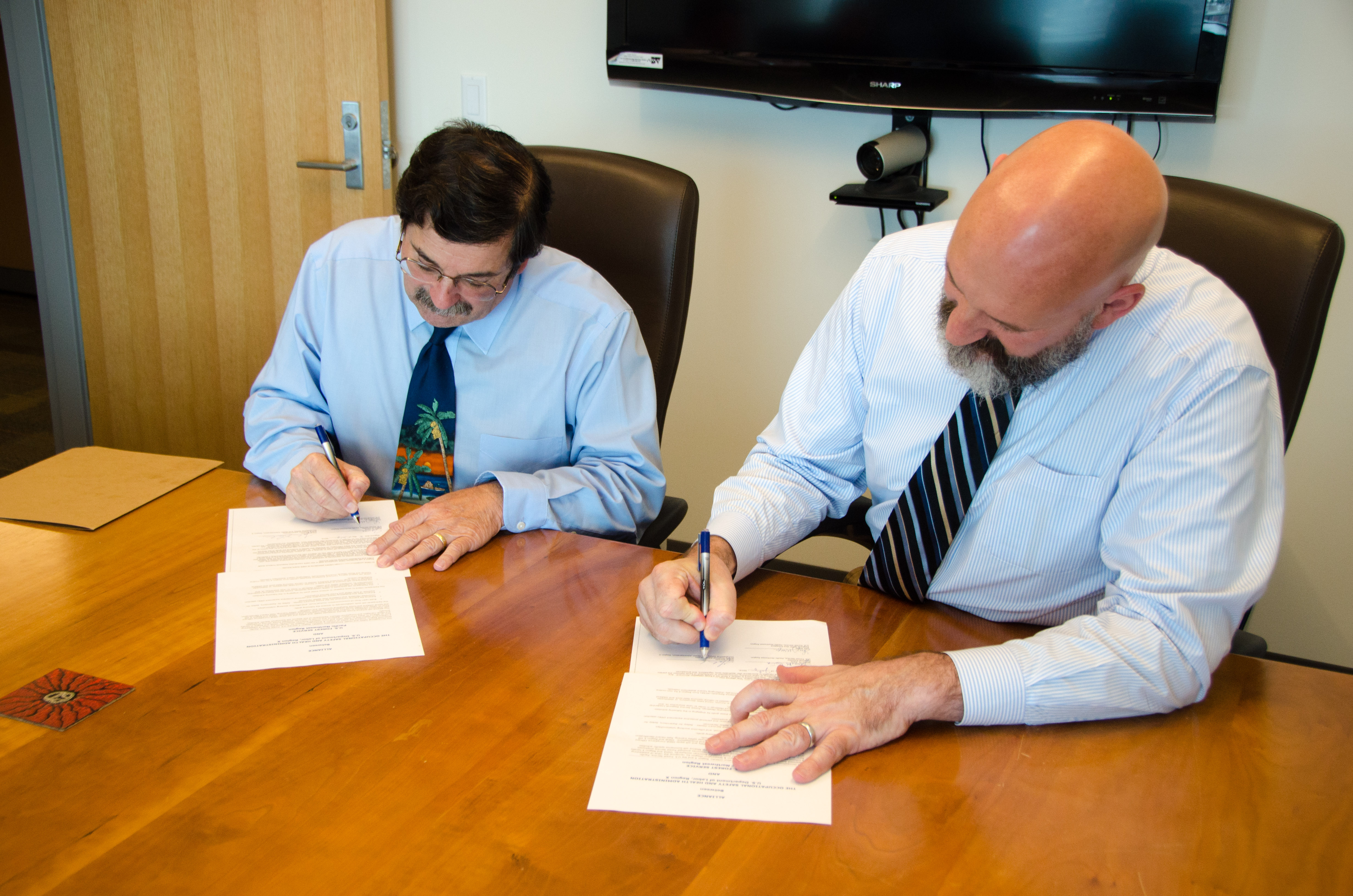 Galen Blanton (right), OSHA's acting regional administrator in Seattle, and James M. Pena, USFS' regional forester, sign a two-year collaboration alliance in Seattle, Washington, on July 8.