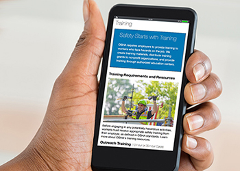 Photograph of hand holding a phone showing OSHA Training page