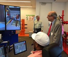 Dr. Michaels observes a demonstration of an oil rig drilling operations simulator.