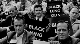 People holding Black Lung Kills posters