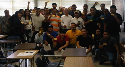 Employees proudly showing their OSHA 10 cards with trainer and OSHA representative, Mark A. Hernandez (in yellow shirt)