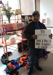 Worker Arturo Soriano holds a sign that reads