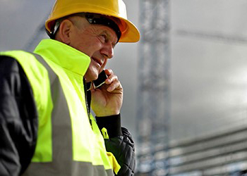Worker wearing hard hat and talking on cell phone