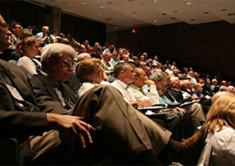 Public stakeholders watch a presentation before participating in a public comment period.