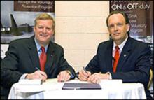 Edwin G. Foulke, Jr., former Assistant Secretary of Labor, OSHA (left) and William C. Anderson, Assistant Secretary of the Air Force, Installations, Environment and Logistics, sign a partnership agreement between the Air Force and Occupational Safety and Health Administration on August 27, 2007 in Washington, D.C. at the annual Voluntary Protection Programs Participants' Association Conference.