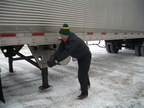 Figure 1 - Manual Cranking to lower the Trailer Landing Gear. Photo Credit: Women In Trucking, Inc.